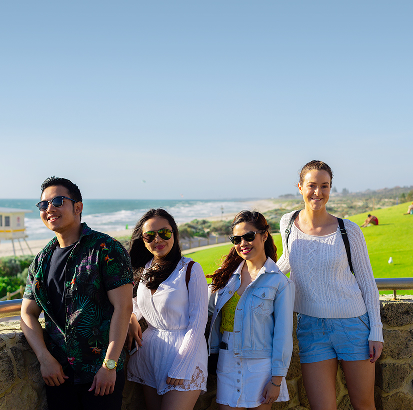 Four students in sunglasses at Scarborough Beach with the ocean and grass behind them.