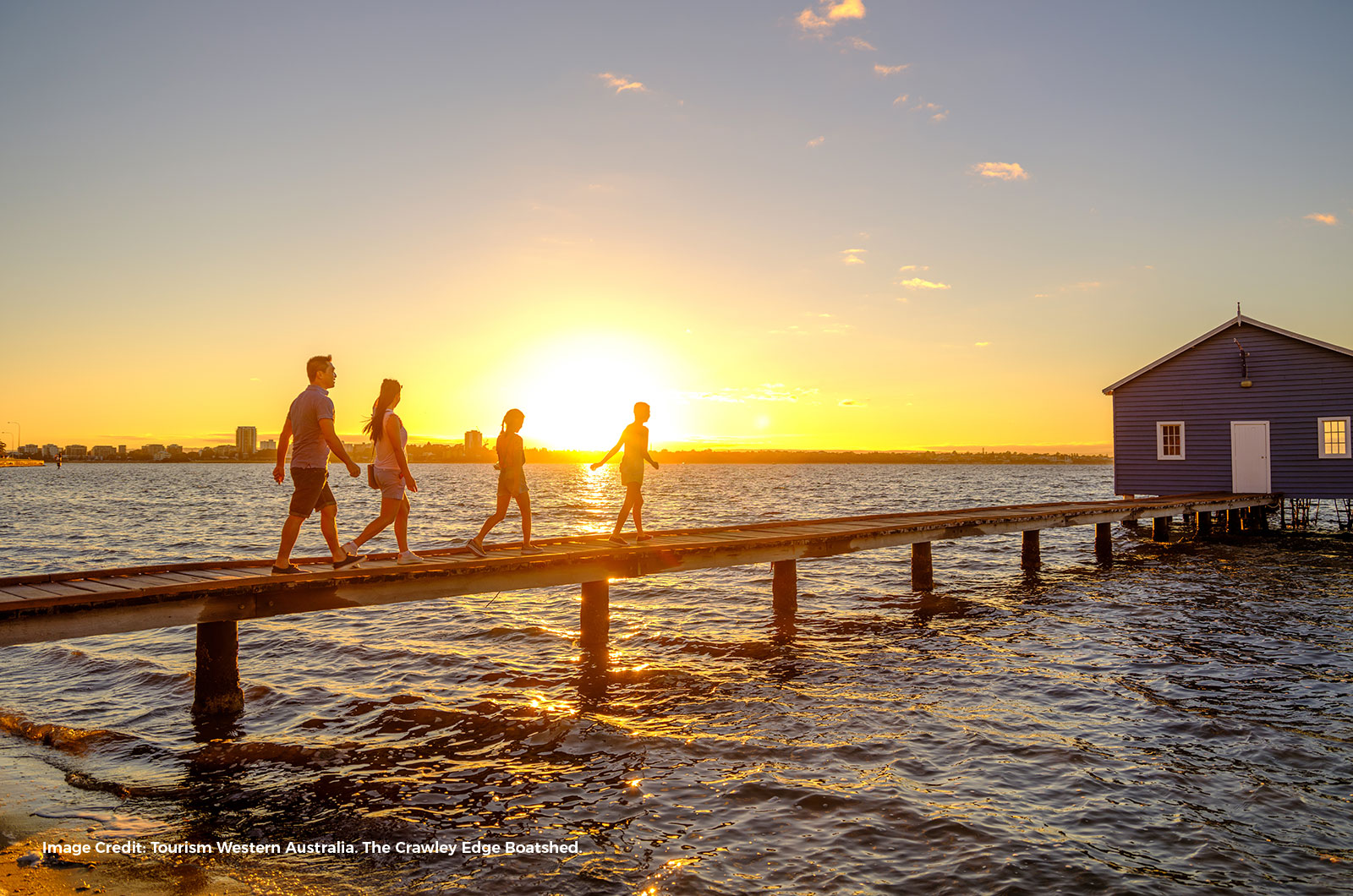 Sunset over Crawley Bay and the Swan River with a family walking on a wooden jetty