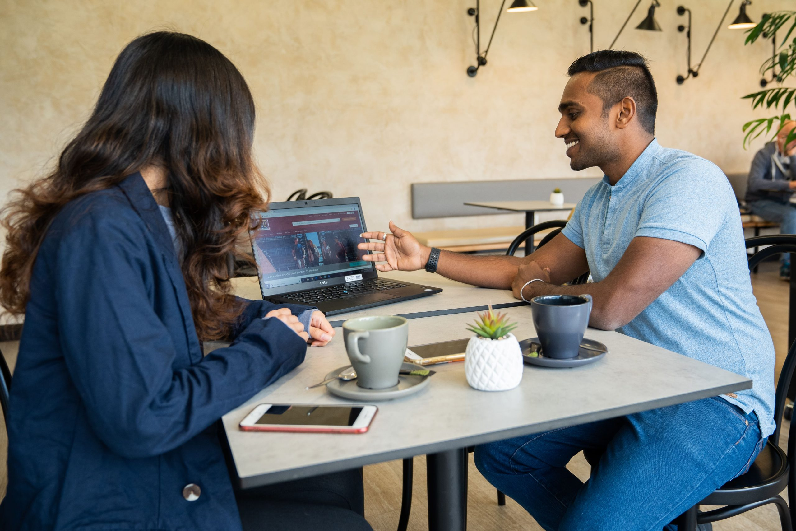 Two students sitting in a cafe working together on a laptop