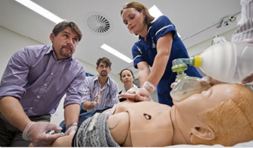 Two adults in foreground with two in background leaning over a dummy, practicing resusitation.