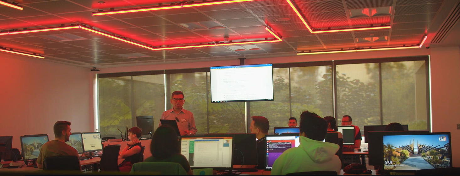 Students in a red lit room working as the threat to an IT system